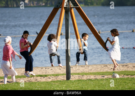 Children playing spinning merry go round carousel in child playground at lakeside in Rotterdam, Netherlands - Stock Photo