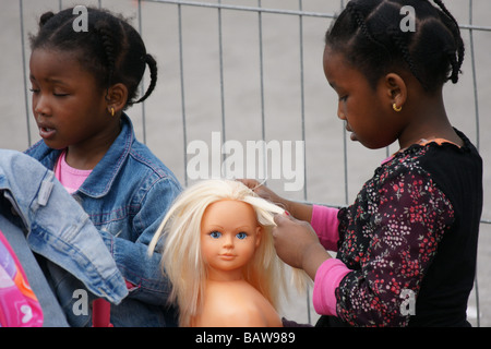 b01b8db6d06710 ... Young black girl child kid playing with blue eyes blonde plastic doll  torso combing hair outdoors