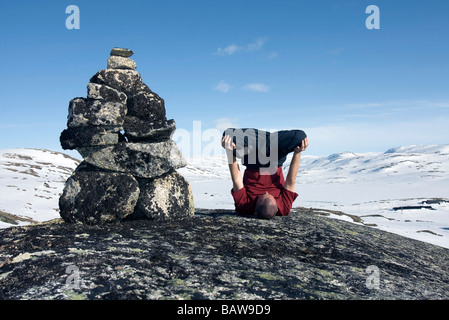 Doug Blane performing an Urdhva Padmasana besides a cairn in Finse Norway in winter - Stock Photo