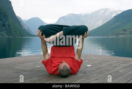 Doug Blane performing an Urdhva Padmasana yoga, upside down lotus on Aurland Fjord, Flam, Norway - Stock Photo