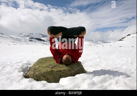 Doug Blane performing an Urdhva Padmasana yoga, upside down lotus on frozen Finse Vatn lake, Finse, Norway - Stock Photo