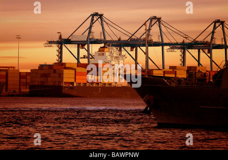 cargo boat by the beach at sunset - Stock Photo