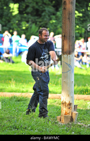 A lumberjack, preparing to chop down a tree in a woodcutters' competition. He will be chopping against the clock. - Stock Photo