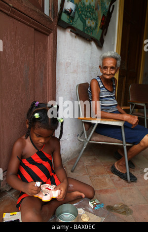 A young Cuban girl painting with her Grandmother. Trinidad, Sancti Spiritus, Cuba - Stock Photo