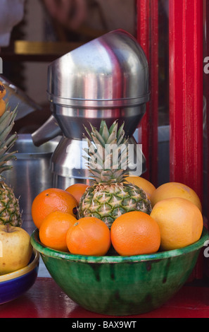 Bowl of oranges grapefruits and pineapple in front of juicing machine in cafe bar Marbella Spain - Stock Photo