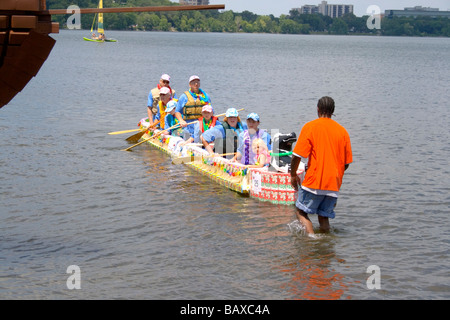 Family in large canoe made from milk cartons finish race on Lake Calhoun. Aquatennial Beach Bash Minneapolis Minnesota - Stock Photo