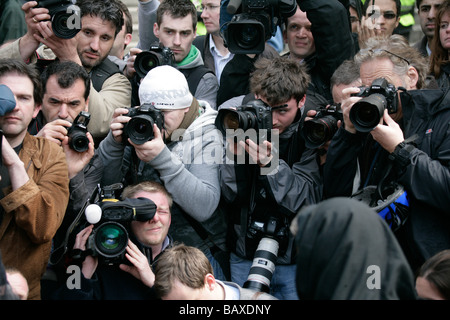 A hoard of news photographers and cameramen cover a news story - Stock Photo