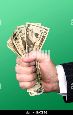 A businessman squeezes a fist full of cash - Stock Photo