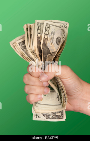 A woman grips a wad of cash hoping she doesn't lose it - Stock Photo