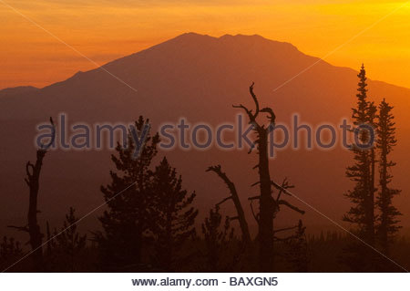 The sun sets behind Mount St. Helens, rendering it in silhouette in this view from Mount Adams, Washington. - Stock Photo