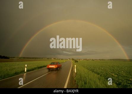 Rainbow over a country road near Glonn, Upper Bavaria, Bavaria, Germany - Stock Photo