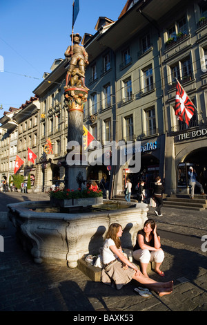 Two young women siting in front of a fountain, Schuetzenbrunnen, Marktgasse, Old City of Berne, Berne, Switzerland - Stock Photo