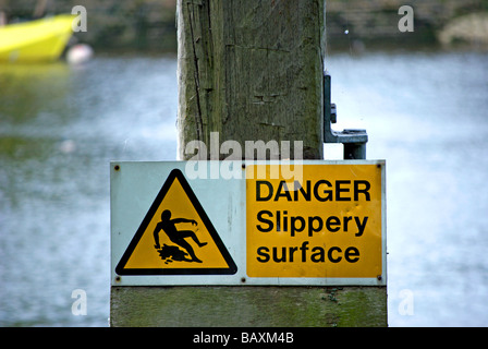 british danger slippery surface sign beside river - Stock Photo