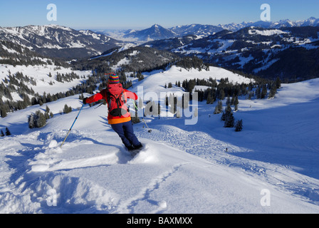 young woman powdering Bleicherhorn, Gruenten in background, Allgaeu range, Allgaeu, Schwabia, Bavaria, Germany - Stock Photo