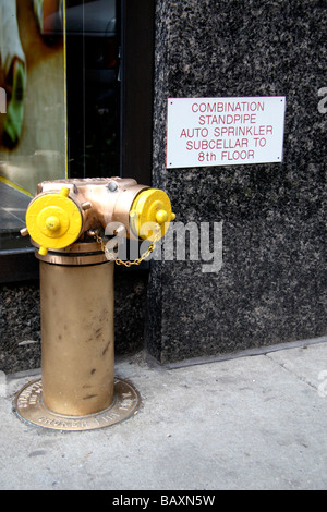 A yellow fire dry riser outside a building in New York. - Stock Photo