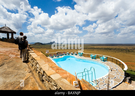Guests looking over swimming pool to savannah, Voi Safari Lodge, Tsavo East National Park, Coast, Kenya - Stock Photo