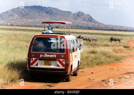 Safari bus on the way in Tsavo East National Park, Coast, Kenya - Stock Photo