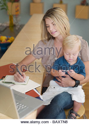 Mother working and holding son on lap - Stock Photo