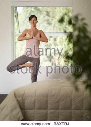 Woman doing yoga in bedroom - Stock Photo