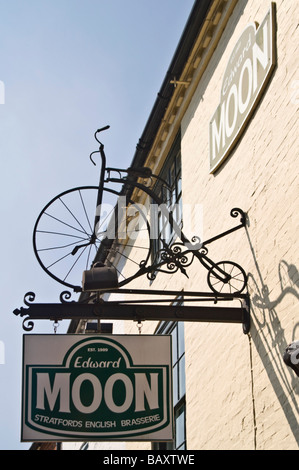 Vertical close up of an elaborate Penny Farthing bicycle wrought iron restaurant sign hanging against a bright blue - Stock Photo