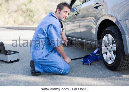 Mechanic changing car's flat tire - Stock Photo