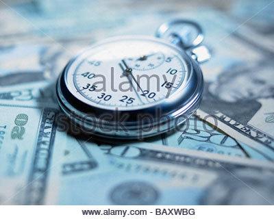 Close up of stopwatch on 20 dollar bills - Stock Photo