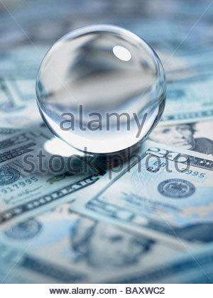 Close up of crystal ball on 20 dollar bills - Stock Photo