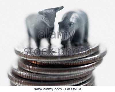 Bull and bear figurines on top of stack of quarters - Stock Photo