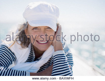 Woman smiling and sitting on boat - Stock Photo