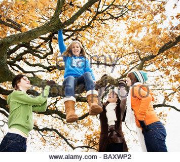 Teenage girls playing in tree - Stock Photo