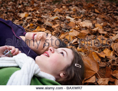 Teenage girls laying in leaves listening to mp3 player - Stock Photo