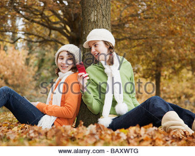 Young girls using cell phones in park - Stock Photo