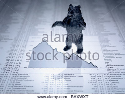Bear figurine on descending line graph and list of share prices - Stock Photo