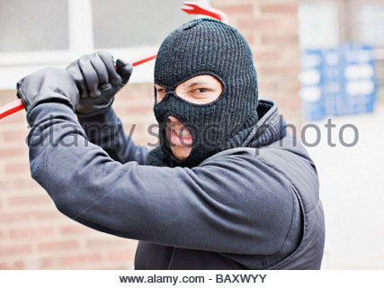 Burglar in ski mask wielding crowbar - Stock Photo