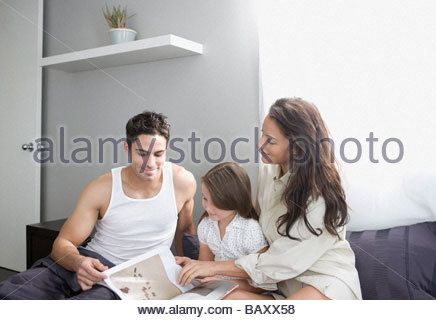 Family reading story in bed together - Stock Photo