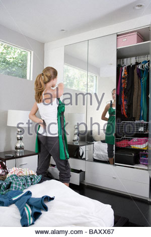 Teenage girl trying on clothes in bedroom - Stock Photo