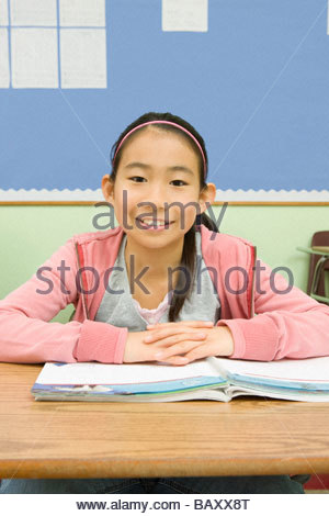 Girl doing school work at desk in classroom - Stock Photo
