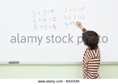 Boy doing multiplication on whiteboard in classroom - Stock Photo