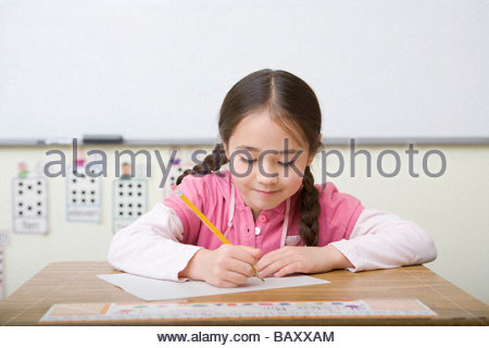 Girl taking test in classroom - Stock Photo