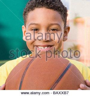 Smiling boy holding basketball - Stock Photo