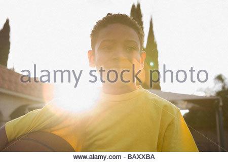 Boy holding basketball outdoors - Stock Photo