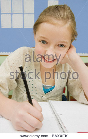 Girl doing school work in classroom - Stock Photo