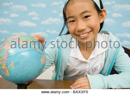 Girl looking at globe in classroom - Stock Photo
