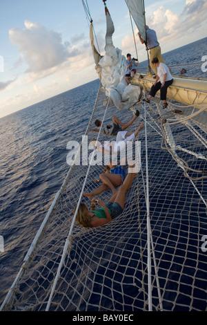 Passengers relaxing in bowsprit net of sailing Cruiseship Star Flyer (Star Clippers Cruises), Rangiroa, The Tuamotus, - Stock Photo