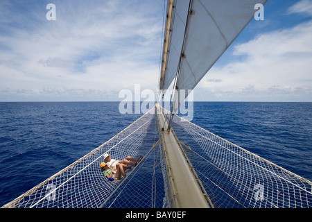 Couple relaxing in bowsprit net of sailing Cruiseship Star Flyer (Star Clippers Cruises), Bora Bora, Society Islands, - Stock Photo
