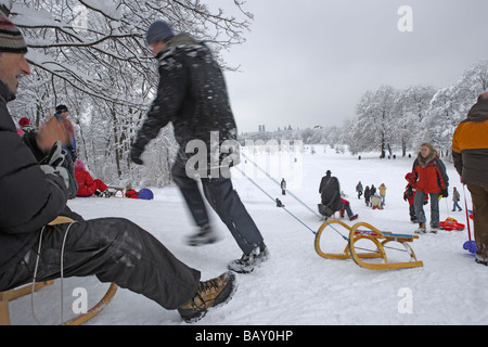 People sledging at English Garden on a winter's day, Munich, Bavaria, Germany - Stock Photo