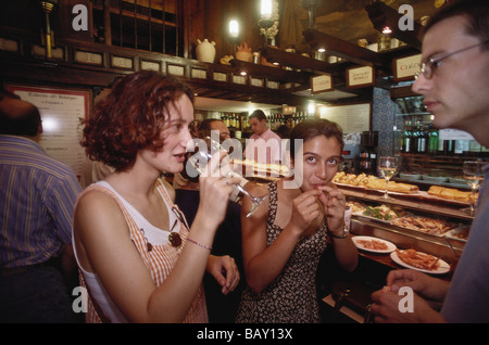 Two young women and a young man drinking wine and tasting some tapas from the counter in a bar in Valladolid, Castilla - Stock Photo