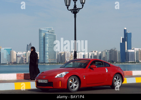 Skyline of Abu Dhabi with luxury car, United Arab Emirates, UAE - Stock Photo