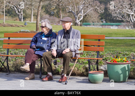 An elderly couple enjoying early spring sunshine on a park bench in Western Canada - Stock Photo