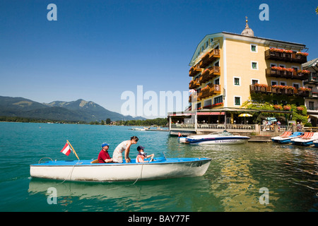 Family in an electric boat arriving St. Wolfgang, Hotel Im Weissen Roessel am Wolfgangsee in background, St. Wolfgang, - Stock Photo